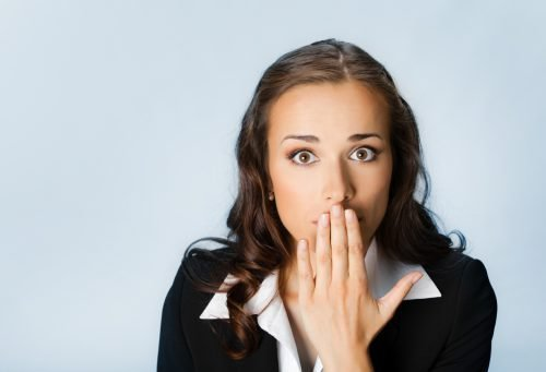 Девушка подносит палец ко рту