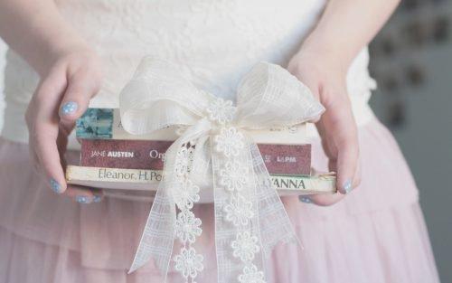 Девушка держит книги в руках