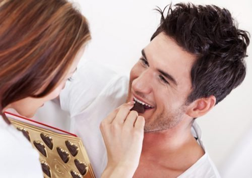 Девушка кормит парня шоколадом
