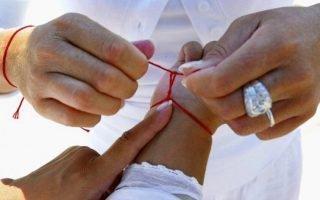 Как правильно завязать красную нитку на левом запястье?