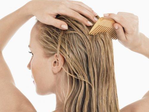 Девушка расчесывает волосы деревянным гребнем