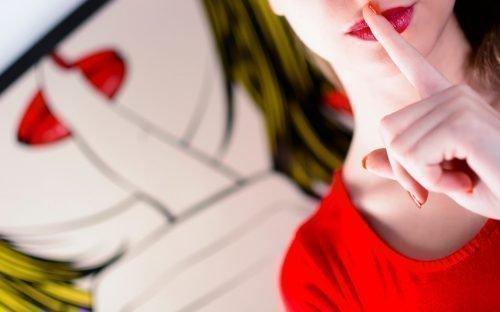 Девушка прикладывает палец к губам